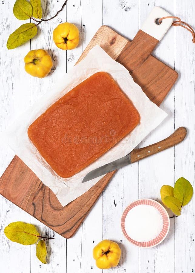 Gelatina casalinga tradizionale del blocchetto della cotogna su un bordo di legno con il coltello immagine stock libera da diritti