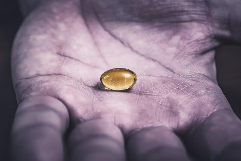 Gelatinpreventivpiller i mitt av ett mörker, smutsigt och använt se handen, bästa sikt fotografering för bildbyråer