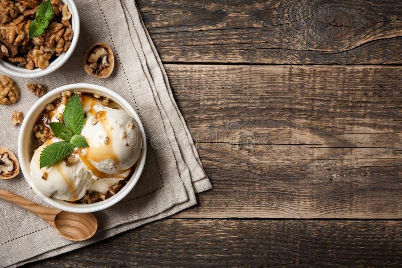Gelato alla vaniglia con i dadi e la salsa del caramello fotografie stock