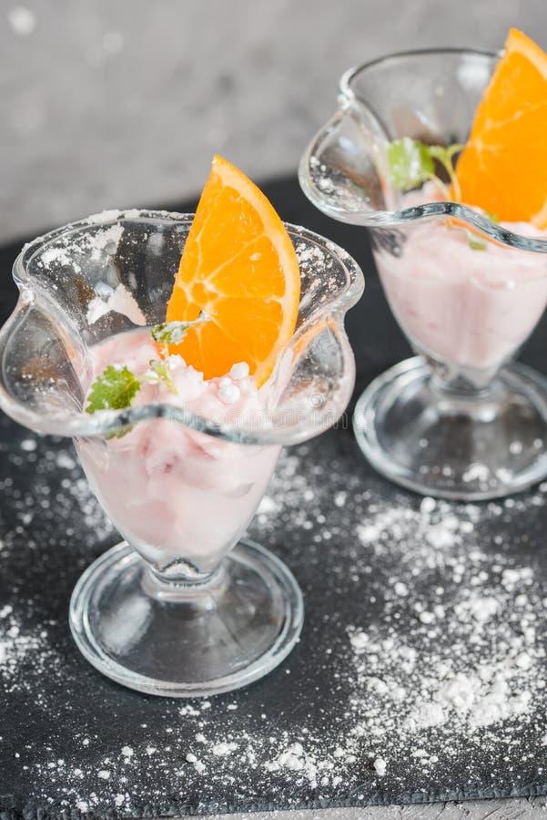 Gelato alla vaniglia con i manghi freschi sulla banda nera Ghiacci il dessert alla panna, yogurt con le fette arancio, le foglie  fotografia stock
