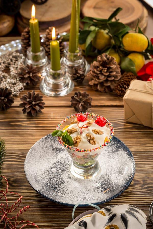 Gelato alla vaniglia delizioso con la ciliegia e le noci rosse in tazza del piatto della coppa gelato su fondo decorato natale fotografie stock