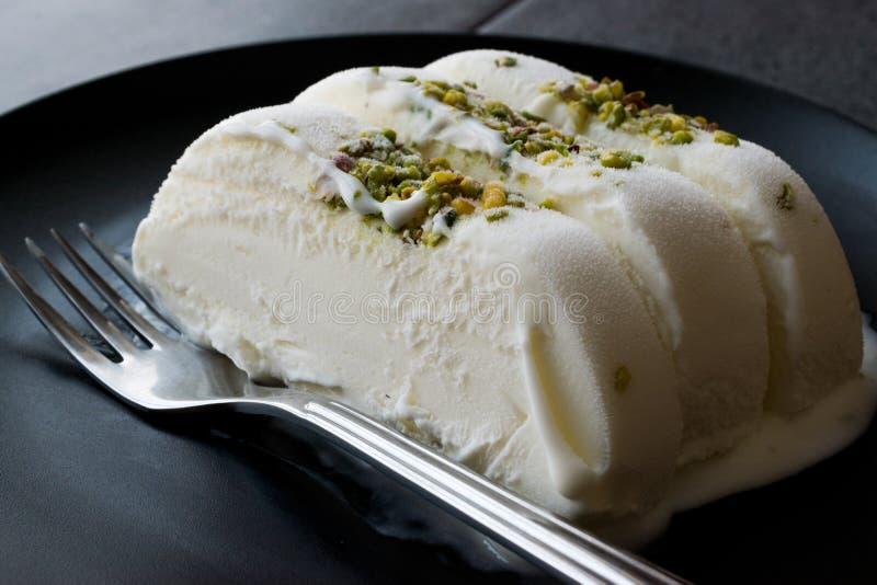 Gelato alla vaniglia di Maras del turco con la parte servita polvere del pistacchio in banda nera immagini stock libere da diritti