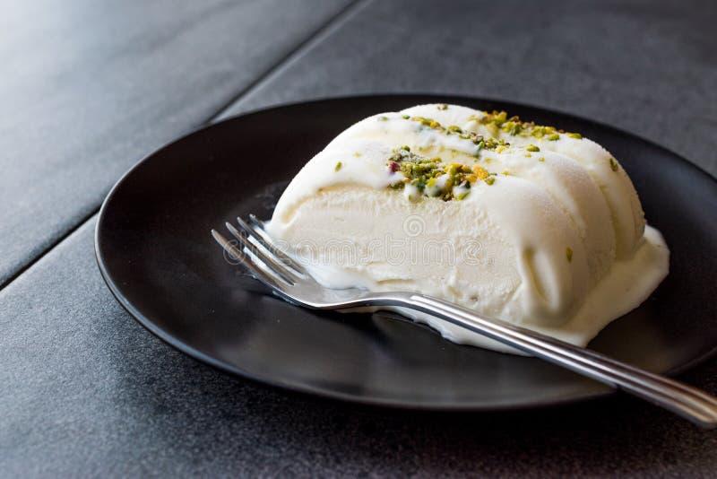 Gelato alla vaniglia di Maras del turco con la parte servita polvere del pistacchio in banda nera immagini stock