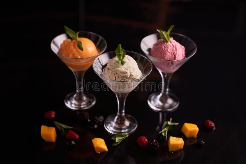Gelato con le barbabietole, mango, formaggio di mascarpone in ciotole di vetro del gelato, decorate con le foglie di menta su un  immagini stock libere da diritti