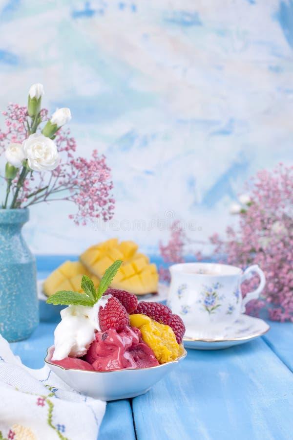 Gelato dei colori differenti su un fondo blu Lamponi e mango Decorazione dei fiori e del caffè di mattina immagine stock