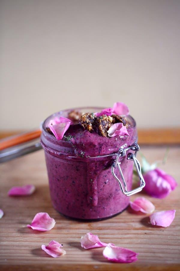 Gelato del mirtillo e della barbabietola o ciotola del frullato, barattolo, con i cracker del seme ed i petali rosa immagine stock libera da diritti