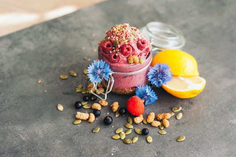 Gelato delizioso del lampone con i semi di zucca ed il seme di canapa, decorati con i fiordalisi blu, ribes nero, limone affettat immagine stock libera da diritti