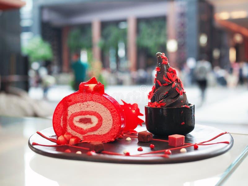 Gelato di carbone nero, gelato alla frutta con bacca di fragola, con aggiunta di cioccolato grattugiato in una ciotola nera, serv fotografie stock