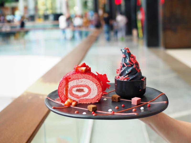 Gelato di carbone nero, gelato alla frutta con bacca di fragola, con aggiunta di cioccolato grattugiato in una ciotola nera, serv immagine stock libera da diritti