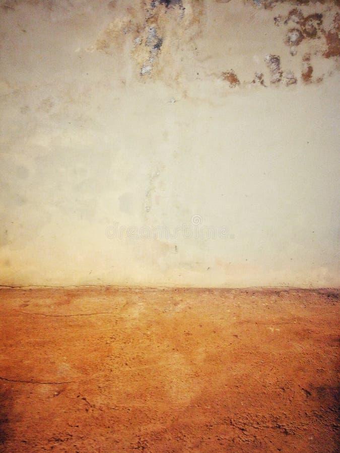 Gelb abgezogene Wand nahe bei rustikalem Zementboden stockfotografie
