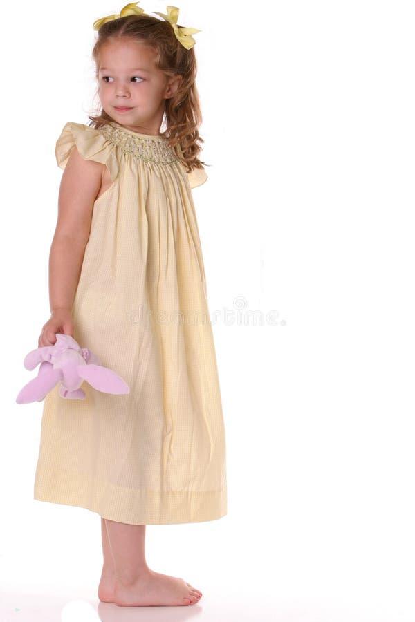 Gelb gekleidetes Mädchenschauen stockfotos