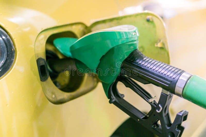 Gelb, Goldauto an einer Tankstelle, die mit Brennstoff gefüllt wird stockbilder