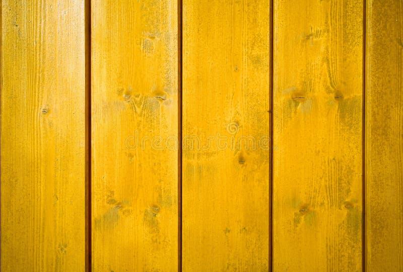 Gelb-orangees gemaltes hölzernes Wandplankensenkrechtes zum Rahmen als einfachem gesättigtem intensivem gelbem Farbholzhintergrun stockfotografie