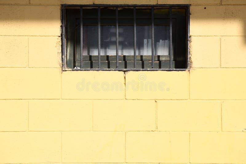 Gelbe Backsteinmauerbeschaffenheit mit Fenster stockfotografie