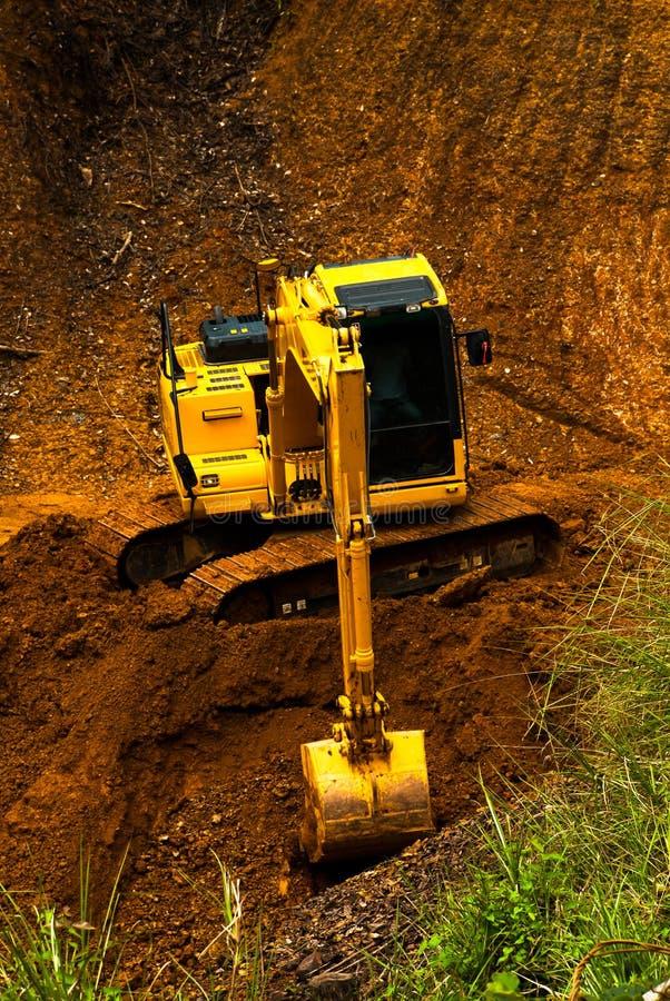 Gelbe Bahn-artige Laderbaggermaschine, die weltbewegendes wor tut lizenzfreies stockfoto