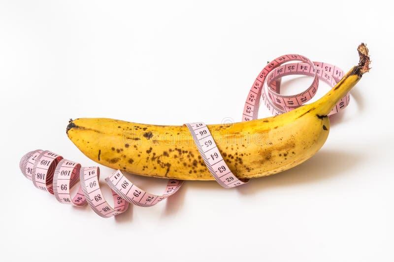 Gelbe Banane mit messendem Band - nähren Sie Konzept stockfoto
