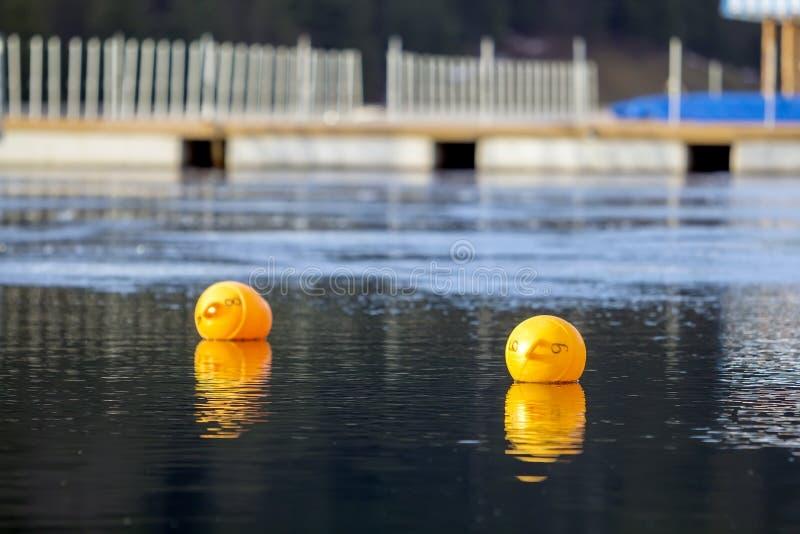 Gelbe Bojen gegen das blaue Wasser Beschränkung auf offenem Wasser stockfotos