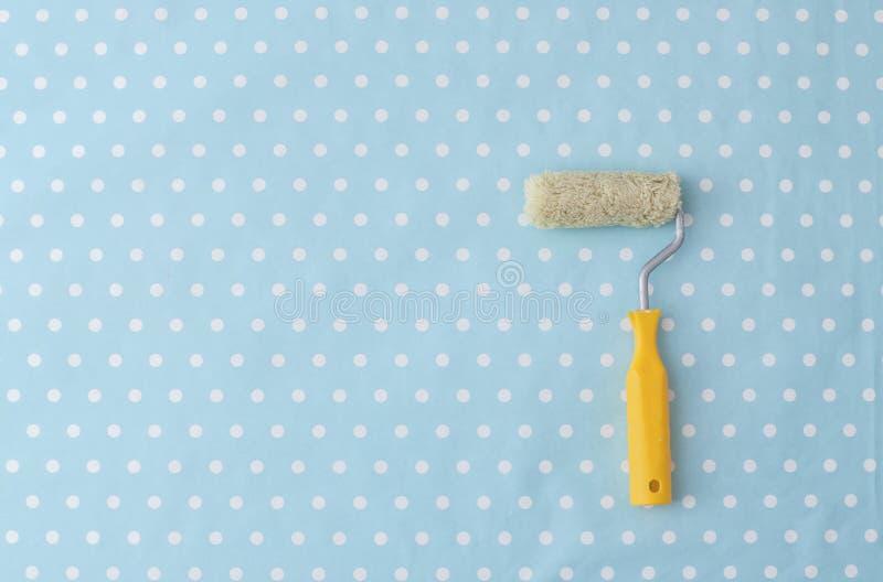 Gelbe Farbenrolle über blauer Tupfentapete lizenzfreie stockfotografie