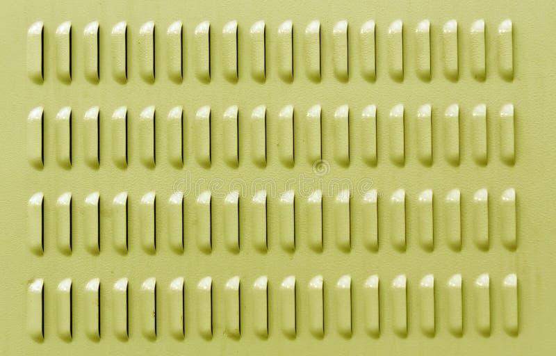 Gelbe Farbmetalloberfläche mit Entlüftungsbohrungen lizenzfreies stockfoto