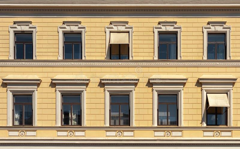 Gelbe Fassade eines schönen Stadtgebäudes Windows mit Gesimsen stockfotografie