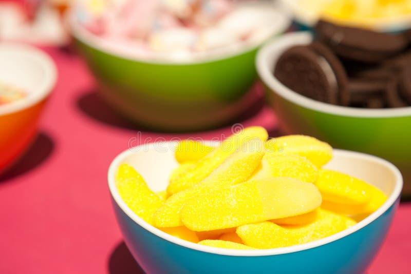 Gelbe Gelees, Plätzchen und andere Süßigkeiten in den hellen Schüsseln stockfotos