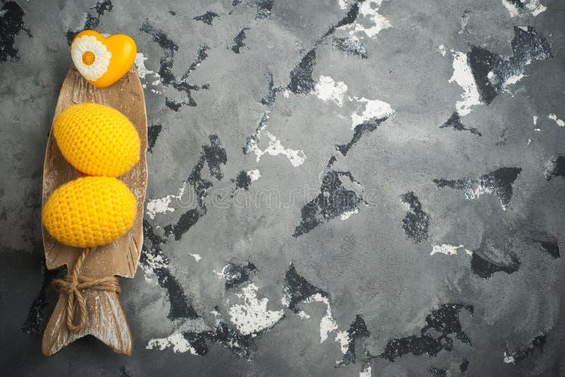 Gelbe gewirkte Ostereier und Herz stockfotos