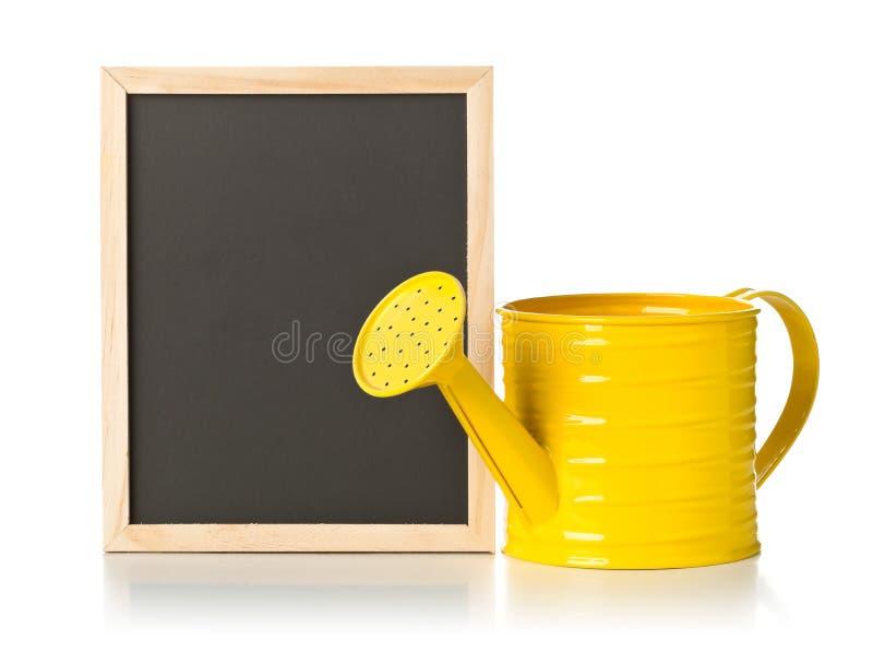 Gelbe Gießkanne mit leerem, freier Raum, schwarze Tafel über weißem Hintergrund lizenzfreie stockbilder