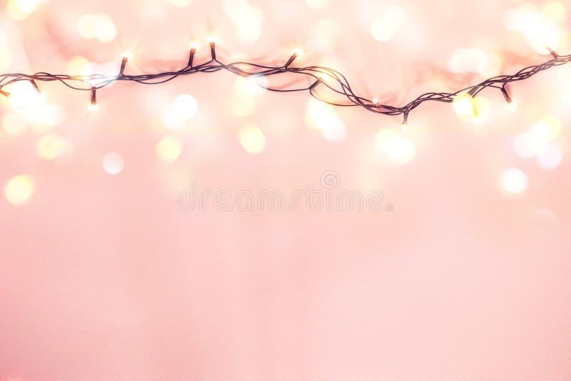Gelbe Girlande auf einem rosa Hintergrund Feiertags-Weihnachtskonzept lizenzfreie stockfotografie