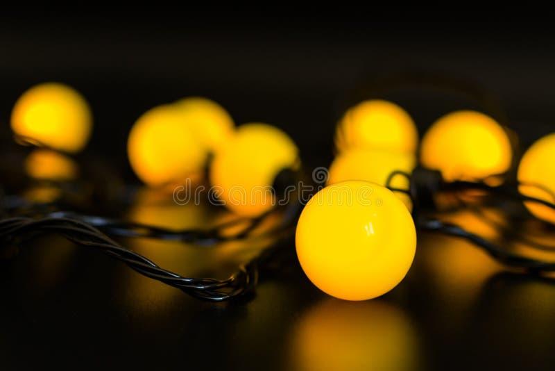 Gelbe glühende Girlande gestapelt auf einem schwarzen Hintergrund mit heller Reflexion stockbilder