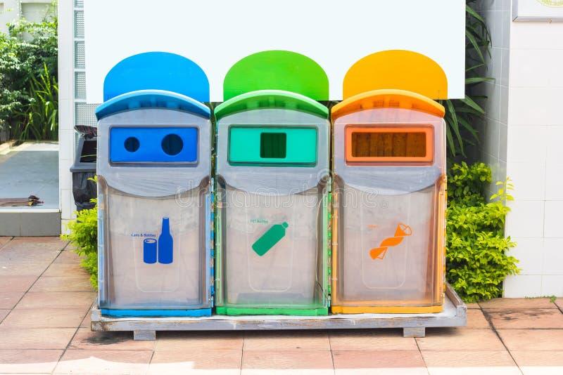 Gelbe, grüne, blaue Papierkörbe mit Recycling-Symbol im Park lizenzfreie stockfotografie
