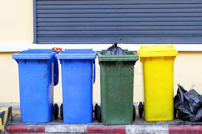 Gelbe, grüne, blaue Wiederverwertungsbehälter auf allgemeinen Bürgersteigen in Phuket, Thailand Wenn die schwarzen Abfalltaschen  stockbild