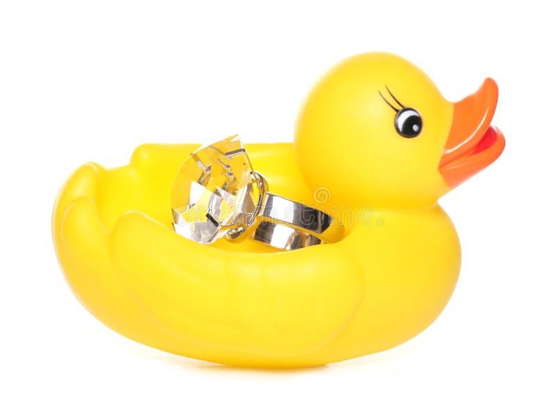 Gelbe Gummiente, die einen Diamantring hält lizenzfreie stockfotos