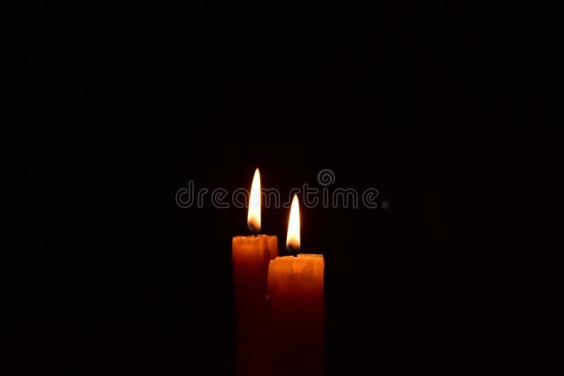 Gelbe helle Kerze, die hell im schwarzen Hintergrund brennt lizenzfreie stockbilder