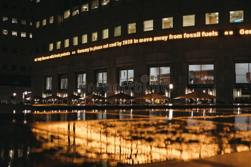Gelbe helle Reflexion im Wasser an einem regnerischen Abend in Canary Wharf, London, Großbritannien lizenzfreie stockfotografie