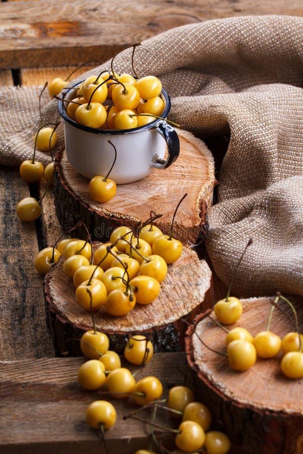 Gelbe Kirsche in einer rustikalen Art auf einem hölzernen Hintergrund Beeren von reifen frischen Kirschen in einer Schale lizenzfreies stockfoto
