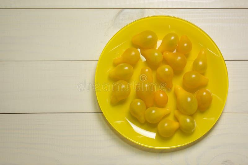 Gelbe Kirschtomaten auf hölzernem Hintergrund der gelben Platte Biologisches Lebensmittel lizenzfreies stockbild