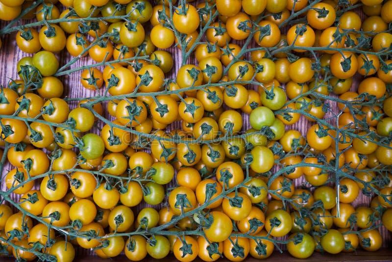 Gelbe Kirschtomaten verzweigen sich auf einen Holztischhintergrund, Nahaufnahme lizenzfreie stockfotos