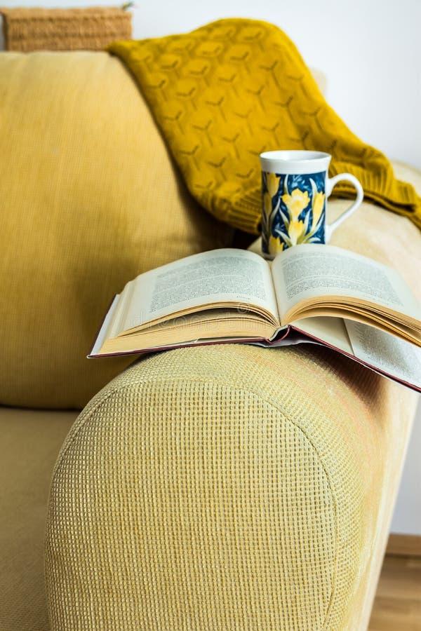 Gelbe Kordsamtinnencouch des Wohnzimmers mit Kissen, gestrickte Strickjacke, offenes Buch, Teeschale, gemütliche entspannende Atm lizenzfreies stockfoto