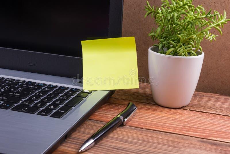Gelbe leere Anmerkung für Anzeige auf Computer-PC-Schirm, Schreibtischtabelle mit suplies hölzernem Schmutz-Weinlesehintergrund stockfoto