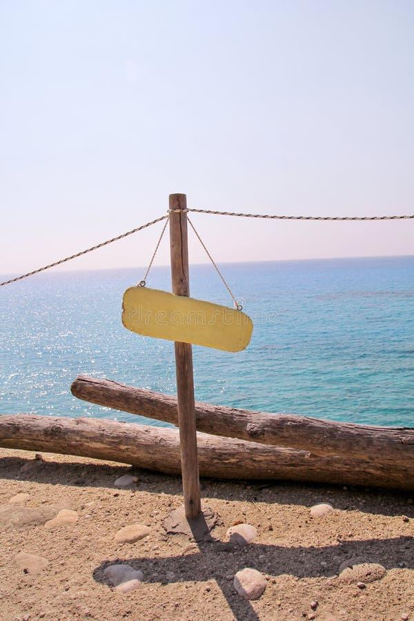 Gelbe leere Anschlagtafel auf sandigem Strand Addieren Sie einfach Ihren Text Strandzeichen durch Meer Leeres rustikales Holzschi stockfotografie