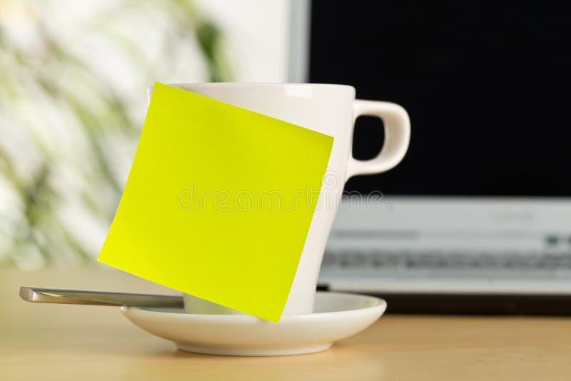 Gelbe leere klebrige Anmerkung über weißen Kaffee oder Teeschale mit Kopienraum vor Laptop auf braunem hölzernem Schreibtisch im  stockbilder