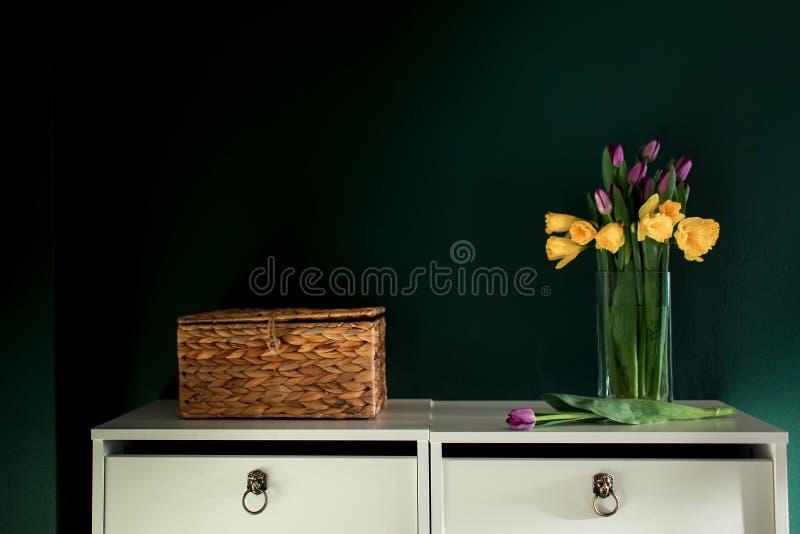 Gelbe Narzisse blüht mit der purpurroten Tulpe, die im Vase mit folgendem bösem Korb der grünen Wand blüht stockbild