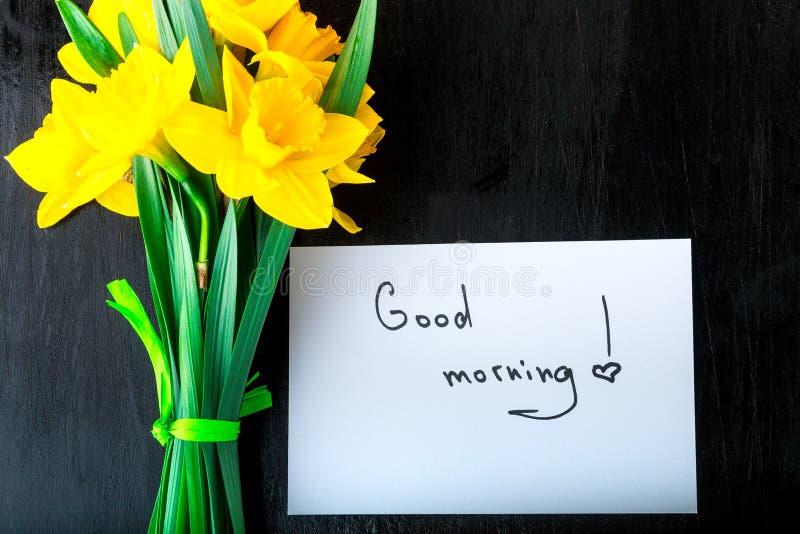 Gelbe Narzisse blüht und zitiert guten Morgen auf weißer rustikaler Tabelle Muttertag oder der Tag der Frauen glückliches neues J lizenzfreie stockfotos
