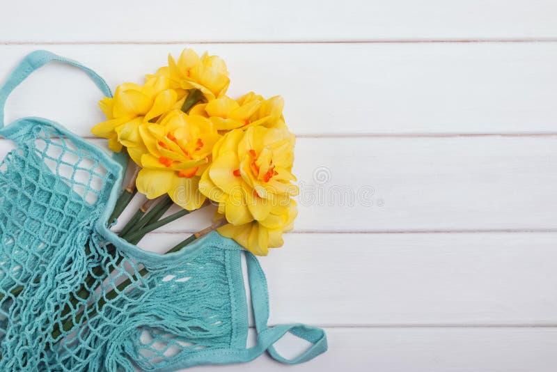 Gelbe Narzissen in der Nettotasche auf dem weißen Holztisch lizenzfreies stockfoto