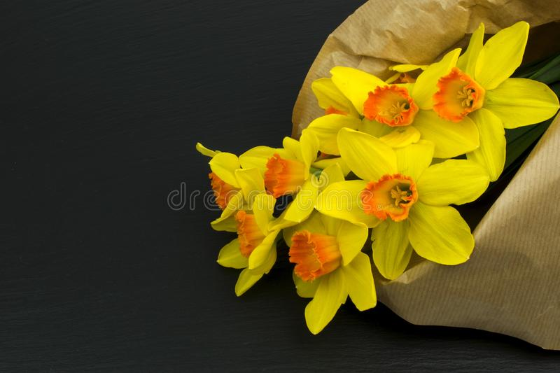 Gelbe Narzissenblumen auf schwarzer Tabelle lizenzfreie stockfotografie