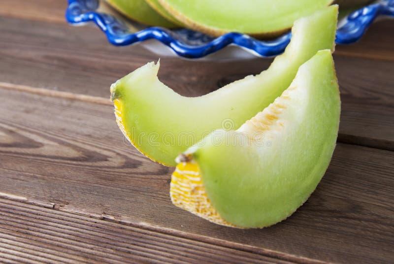 Gelbe neue Melonenscheiben der Kantalupe lokalisiert mit blauer Platte der schönen Weinlese auf Hintergrund, Holztischhintergrund stockfotografie