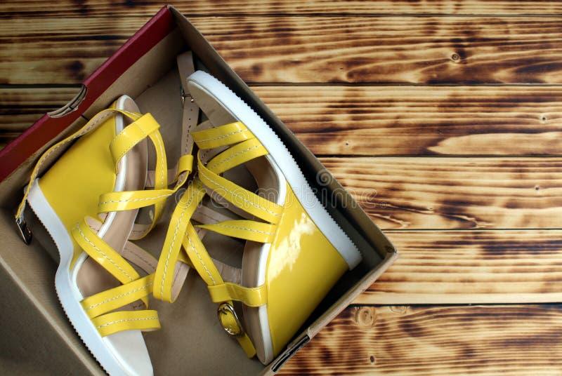 Gelbe neue Sandalen sind in einer Pappschachtel stockfoto