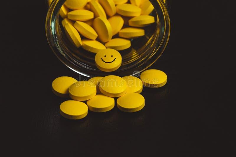 gelbe Pillen, die aus einem gestürzten Tablettenfläschchen verschüttet werden - eine smileygesichtspille heraus - Antikrisenkonze lizenzfreie stockfotos