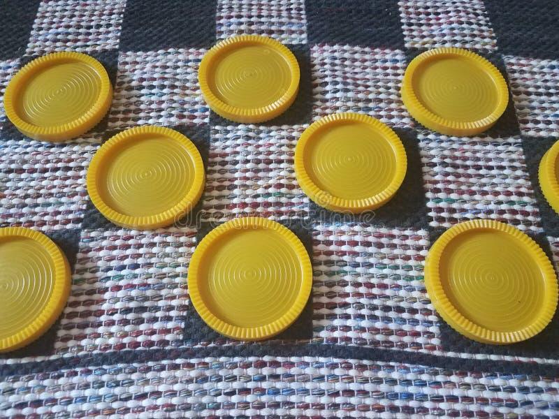 Gelbe Plastikkontrolleure auf Gewebeschachbrett stockfotografie