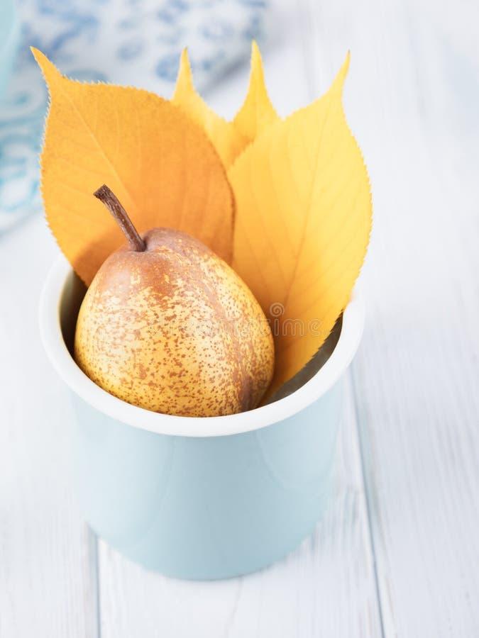 Gelbe reife Birne und Herbstlaub in emaillierter Schale auf einem weißen Hintergrund stockfoto